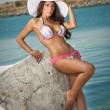Fashion portrait of young sexy brunette girl in swimsuit  hat at the beach. Sensual attractive woman  wearing swimsuit and nice tits. Woman with perfect body wearing big hat relaxing on the beach. — Stock Photo