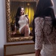 Beautiful girl in a short white dress with glass of wine looking into mirror.Sensual woman wearing a white short dress in the old hotel.Sensual elegant young woman in white dress looking into mirror — Stock Photo