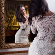 Beautiful girl in a short white dress looking into mirror.Sensual woman wearing a white short dress in the old hotel.Sensual elegant young woman in white dress looking into mirror — Foto de Stock