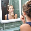 A beautiful teen girl putting lipstick and checking as she looks like. Teen girl happy with their appearance in the mirror using lipstick. — Стоковая фотография
