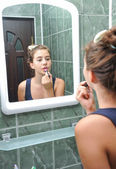 A beautiful teen girl putting lipstick and checking as she looks like. Teen girl happy with their appearance in the mirror using lipstick. — Stock Photo
