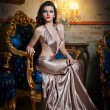 Young beautiful luxurious woman in long elegant dress. Beautiful young woman in a luxurious classic interior. Seductive brunette woman in luxury manor, vintage style — Stock Photo