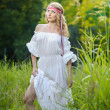 Portrait of a sensual young blonde female on field in sexy white long dress. Portrait of beautiful blonde girl outdoor. Beautiful woman enjoying green field, pretty girl relaxing outdoor — Stock Photo