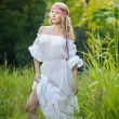 Portrait of a sensual young blonde female on field in sexy white long dress. Portrait of beautiful blonde girl outdoor. Beautiful woman enjoying green field, pretty girl relaxing outdoor — Foto de Stock