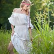 Portrait of a sensual young blonde female on field in sexy white long dress. Portrait of beautiful blonde girl outdoor. Beautiful woman enjoying green field, pretty girl relaxing outdoor — Foto Stock