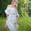 Portrait of a sensual young blonde female on field in sexy white long dress. Portrait of beautiful blonde girl outdoor. Beautiful woman enjoying green field, pretty girl relaxing outdoor — Photo