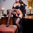 Attractive sexy brunette with black lingerie posing challenging. Portrait of sensual woman wearing black bra in classic boudoir scene. Long hair brunette wearing black boudoir outfit in vintage room — Stock Photo