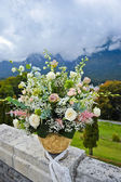 Large pot with flowers and landscape with mountains behind.Multicolored flowers in a large vase in the mountain garden .Large Flower Pot outdoor — Stock Photo