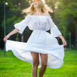Young woman dancing on fresh green grass in a park. Portrait of girl in a meadow. Romantic young woman posing outdoor. Attractive woman in long white dress with a flower power look — Stock fotografie