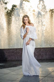 Attractive girl in white long dress sitting in front of a fountain in the summer hottest day. Girl with dress partly wet posing near a fountain. Blonde women near the fountain in a ballet position — Stock Photo