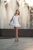 Attractive girl in white short dress sitting in front of a fountain in the summer hottest day. Girl with dress partly wet dancing. Beautiful blonde women near the fountain in a ballet position — Stock Photo