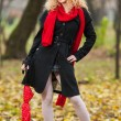 Attractive young woman in a autumn fashion shoot. Beautiful fashionable young girl with red umbrella , red cap and red scarf in the park — Stock Photo #32743279