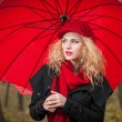 Attractive young woman in a autumn fashion shoot. Beautiful fashionable young girl with red umbrella, red cap and red scarf in the park. — Stock Photo