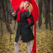 Attractive young woman in a autumn fashion shoot. Beautiful fashionable young girl with red umbrella, red cap and red scarf in the park. — Stock Photo #33227555