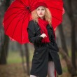 Attractive young woman in a autumn fashion shoot. Beautiful fashionable young girl with red umbrella, red cap and red scarf in the park. — Stock Photo #33227573