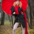 Attractive young woman in a autumn fashion shoot. Beautiful fashionable young girl with red umbrella, red cap and red scarf in the park. — Stock Photo #33227581