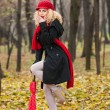 Attractive young woman in a autumn fashion shoot. Beautiful fashionable young girl with red umbrella, red cap and red scarf in the park. — Stock Photo #33227591