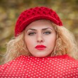 Attractive blonde girl with red cap looking over red umbrella outdoor shoot. Attractive young woman in a autumn fashion shoot. — Stock Photo #33228605