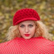 Attractive blonde girl with red cap looking over red umbrella outdoor shoot. Attractive young woman in a autumn fashion shoot. — Stock Photo