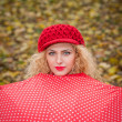 Attractive blonde girl with red cap looking over red umbrella outdoor shoot. Attractive young woman in a autumn fashion shoot. — Stock Photo #33228609