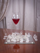 Glass of wine near chess pieces on a chessboard. Set of chess figures on the playing board near a glass of wine on a table — Foto de Stock
