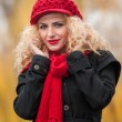 Attractive young woman in a autumn fashion shoot. Beautiful fashionable young girl with red cap and red scarf in the park. Blonde women with red accessories posing outdoor. Nice fair hair girl — Stock Photo #33759575