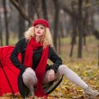 Attractive young woman in a autumn fashion shoot. Beautiful fashionable young girl with red umbrella, red cap and red scarf in the park. Blonde women with red accessories posing outdoor — Stock Photo #33759611