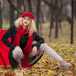 Stock Photo: Attractive young womin autumn fashion shoot. Beautiful fashionable young girl with red umbrella, red cap and red scarf in park. Blonde women with red accessories posing outdoor