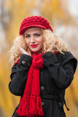 Attractive young woman in a autumn fashion shoot. Beautiful fashionable young girl with red cap and red scarf in the park. Blonde women with red accessories posing outdoor. Nice fair hair girl — Stock Photo