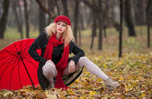 Attractive young woman in a autumn fashion shoot. Beautiful fashionable young girl with red umbrella, red cap and red scarf in the park. Blonde women with red accessories posing outdoor — Stock Photo