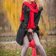 Attractive young woman in a autumn fashion shoot. Beautiful fashionable young girl with red cap and red scarf in the park. Blonde women with red accessories posing outdoor. Nice fair hair girl — Stock Photo #33780527