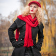Attractive young woman in a autumn fashion shoot. Beautiful fashionable young girl with red cap and red scarf in the park. Blonde women with red accessories posing outdoor. Nice fair hair girl — Stock Photo #33780529