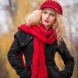 Attractive young woman in a autumn fashion shoot. Beautiful fashionable young girl with red cap and red scarf in the park. Blonde women with red accessories posing outdoor. Nice fair hair girl — Stock Photo #33780531