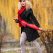 Attractive young woman in a autumn fashion shoot. Beautiful fashionable young girl with red umbrella, red cap and red scarf in the park. Blonde women with red accessories posing outdoor — Стоковая фотография