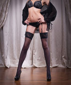 Sexy beautiful body shoot of young woman wearing black lingerie and stockings. Long legs in black stockings indoor. — Stock Photo