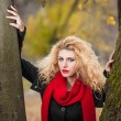 Attractive young woman in a autumn fashion shoot. Beautiful fashionable young girl with red scarf in the park. Blonde women with red accessories posing outdoor. Nice fair hair girl between two trees — Stock Photo #34246375