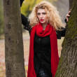 Attractive young woman in a autumn fashion shoot. Beautiful fashionable young girl with red scarf in the park. Blonde women with red accessories posing outdoor. Nice fair hair girl between two trees — Stock Photo #34246381