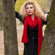 Attractive young woman in a autumn fashion shoot. Beautiful fashionable young girl with red scarf in the park. Blonde women with red accessories posing outdoor. Nice fair hair girl between two trees — Stock Photo #34246383