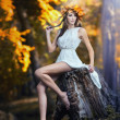 Stock Photo: Portrait of beautiful girl in forest. girl with fairy look in autumnal shoot. Girl with Autumnal Make up and Hair style. romantic women with short white dress posing in autumnal park