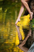 Beautiful woman legs in water in the forest. fairy tale — Stock Photo