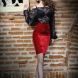 Charming young brunette woman in black lace blouse, red skirt and high heels near the brick wall. Sexy gorgeous young woman near old wall. Full length portrait of a sensual woman with long hair — Foto de Stock
