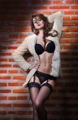 Beautiful brunette woman in black sensual lingerie posing provocatively in front of a brick wall. Young model posing in front of brick wall. Posing pretty. Caucasian model standing near red brick wall — Stock Photo