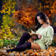 Young caucasian sensual woman reading a book in a romantic autumn scenery.Portrait of pretty young girl in the forest in autumn day.Fashion portrait of a beautiful young woman in autumn forest — Stok fotoğraf