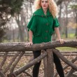 Beautiful woman posing in park during autumn season. Blonde girl wearing green blouse posing outdoor. Long fair hair girl with green sweater in autumnal park. — Stockfoto