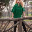 Beautiful woman posing in park during autumn season. Blonde girl wearing green blouse posing outdoor. Long fair hair girl with green sweater in autumnal park. — Foto Stock