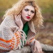 Beautiful woman posing in park during autumn season. Blonde girl wearing green blouse and big shawl posing outdoor. Long fair hair girl with green sweater under a shawl relaxing in autumnal park. — Foto de Stock   #35111393