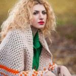 hermosa mujer posando en el parque durante la temporada de otoño. chica rubia vestida con blusa verde y mantón grande posando al aire libre. chica de pelo largo rubio con suéter verde bajo un chal relajante en el parque otoñal — Foto de Stock   #35111397