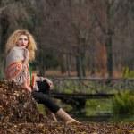 hermosa mujer posando en el parque durante la temporada de otoño. chica rubia vestida con blusa verde y mantón grande posando al aire libre. chica de pelo largo rubio con suéter verde bajo un chal relajante en el parque otoñal — Foto de Stock   #35111429