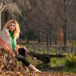 Beautiful woman posing in park during autumn season. Blonde girl wearing green blouse and big shawl posing outdoor. Long fair hair girl with green sweater under a shawl relaxing in autumnal park. — Stockfoto