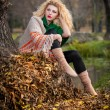 Beautiful woman posing in park during autumn season. Blonde girl wearing green blouse and big shawl posing outdoor. Long fair hair girl with green sweater under a shawl relaxing in autumnal park. — Foto de Stock